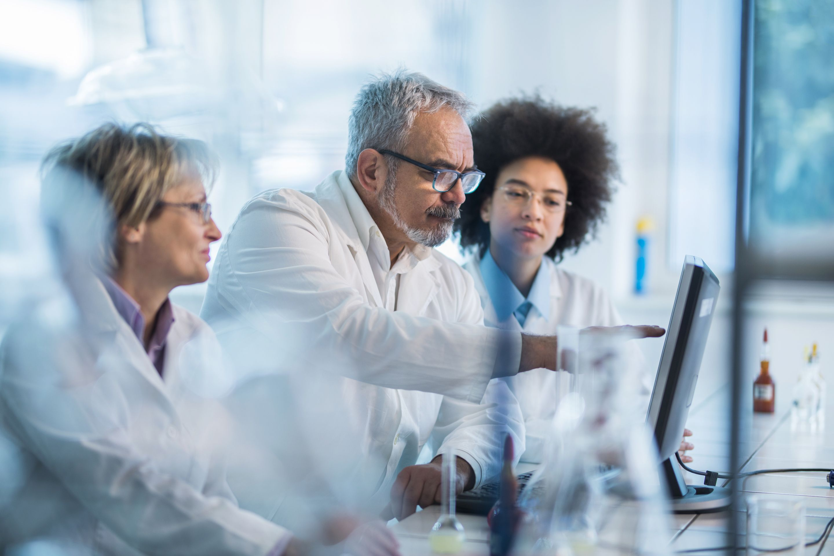 Female and male scientists in lab using touchscreen