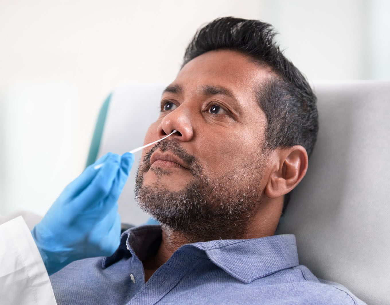 Nhân viên y tế thực hiện việc lấy dịch mũi họng của một bệnh nhân